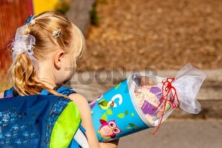 Little girl standing in front of the school building holding her candy cone