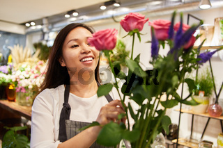 Floristin bindet einen Blumenstrauß mit Rosen