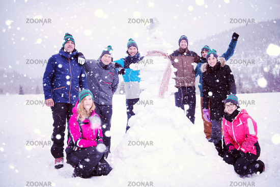 group portait of young people posing with snowman