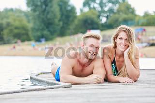 Junges Paar liegt entspannt auf einem Steg