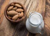 Jar of almond milk with almond nuts on wooden background