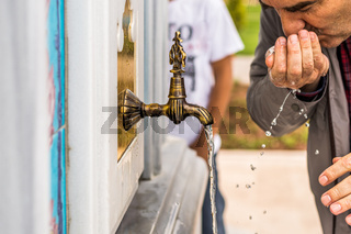 Thirsty man drinking water from an antique Turkish faucet on a marble wall