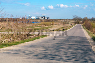 in the distance the construction of the plant, secondary country road