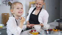 Little girl talking with her mother which cooking cottage cheese pancakes in the kitchen