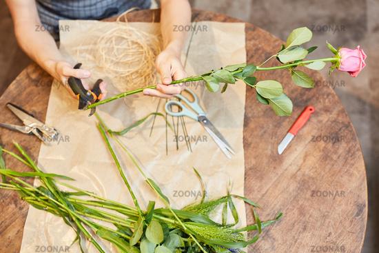Florist kürzt mit Blumenschere eine Rose
