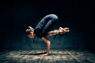 Young woman practicing yoga doing forearm stand crane pose asana in dark room
