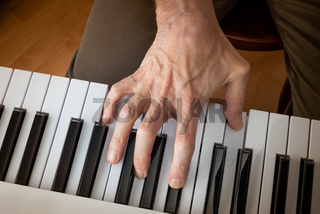 Hand of a musician playing a music keyboard