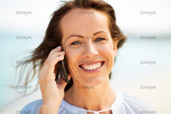 happy woman calling on smartphone on summer beach