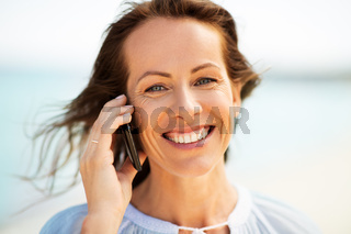 happy woman calling on smartphone on summer beach