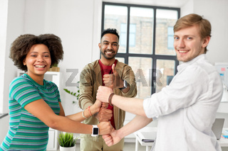 happy creative team making high five at office