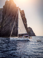 Sailboat floating in harbour against cliff in summer
