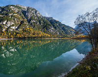 Autumn peaceful alpine lake Durrensee or Lago di Landro.  Snow-capped Cristallo rocky mountain group behind, Dolomites, Italy, Europe. Picturesque traveling, seasonal and nature beauty concept scene.