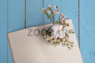 Vase of flowers and open notebook on wooden table