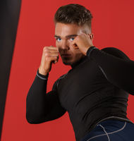 Photo of boxer fulfills blows, on red background