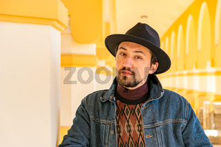 Portrait of a stylish handsome young man with a scarf outdoors.  A serious man wearing a hat and a denim jacket looking confident at the camera