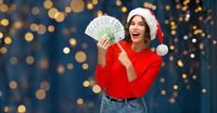 happy woman in santa hat with money on christmas