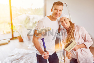 Paar beim Malern und Tapezieren bei Renovierung