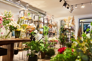 Mann als Florist im Blumenladen zwischen Pflanzen