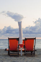 Beach chairs and umbrella at sunset on an italian beach in late summer