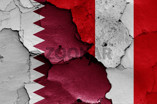 flags of Qatar and Peru painted on cracked wall