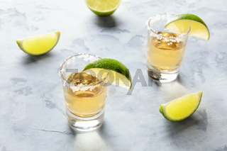 Golden tequila shots with lime slices and salt