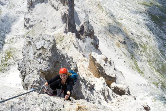 attractive blonde female climber on a steep Via Ferrata in the Italian Dolomites