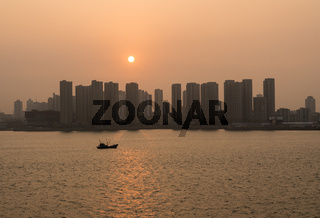 Sun rising behind the tall city skyline of Qingdao in China