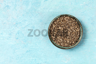 Chia seeds in a bowl, overhead shot on a blue background with copyspace