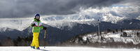 Young skier with ski poles in sun mountains and cloudy gray sky before blizzard