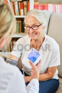 Ärztin misst Blutdruck bei einer lächelnden Seniorin