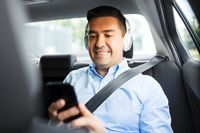 passenger with headphones using smartphone in car