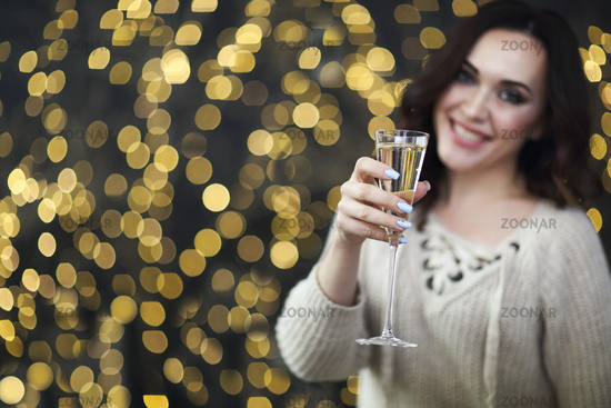 Smiling woman in the sweater with glass of champagne over lights background