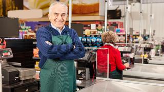 Senior als Kassierer an der Supermarkt Kasse