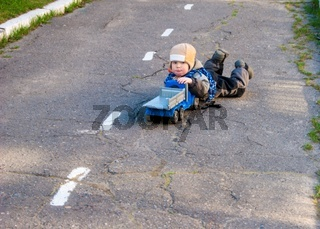 A small boy of three years old is lying on the pavement near the kindergarten with his toy truck
