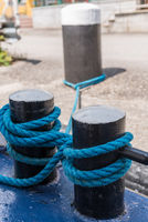 Mooring rope turned around bollard to secure ship at mooring - close-up