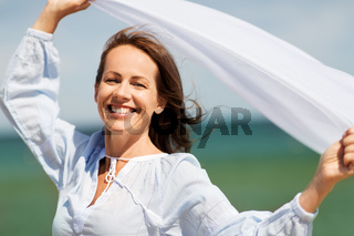 happy woman with shawl waving in wind on beach