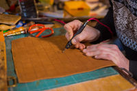 Skinner making decorative details on leather playing field