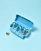 Paper tray with eyeballs on a pastel blue background.