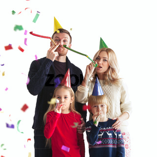Family blowing party trumpets with confetti