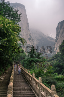 Tourists on steps on mountain trail in Huashan mountain