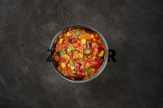 Chili con carne, a Mexican stew with beans, ground meat, corn, and chilli peppers, shot from the top on a dark background