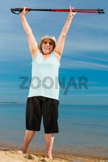 Senior woman warming up with walking poles