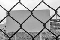 Blank danger or warning sign through wire mesh fence
