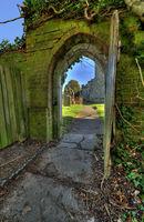 ld open wooden door looking into church graveyard. woodchurch Kent