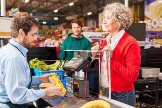 Kundin an der Supermarkt Kasse schaut auf Kassierer