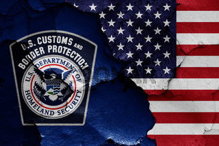 flags of U.S. Customs and Border Protection and USA painted on cracked wall