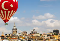 Galata tower Istanbul Turkey. Air balloons star and crescent flying in the blue sky. Travel concept.