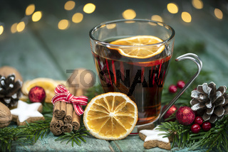 Mulled wine with spices and fir cones on wood