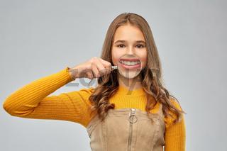 teenage girl shows teeth through magnifying glass