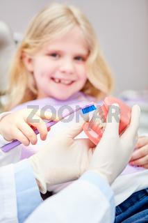 Kind als Patient lernt Zähne putzen beim Zahnarzt